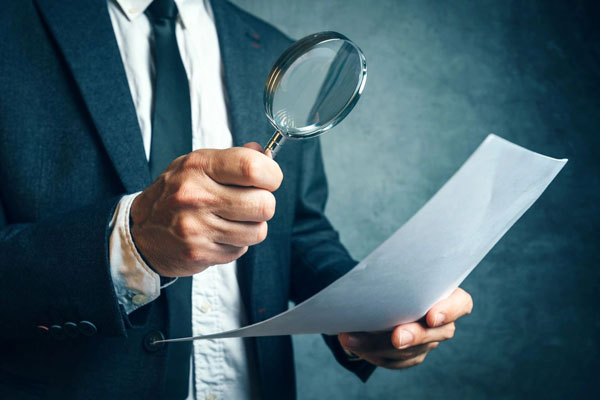 How do you choose an accountant - man with magnifying glass looking at letter of engagement.